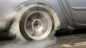 De belemmeringsraceauto brandt rubber van zijn banden stock videobeelden