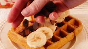 De Belgische wafels met chocoladeschilfers bestrooiden wapen, een gebroken tegel, banaanclose-up stock videobeelden