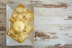 De Belgische wafels met gesmolten witte chocolade, vanilleroomijs en kokosnoot schilfert op lichte houten achtergrond af stock fotografie