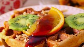 De Belgische wafels met kiwi en sinaasappel gieten stroop, bovenste laagje, karamel, gekookte condens, stock videobeelden