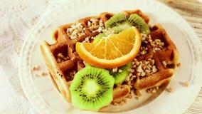 De Belgische wafels met kiwi en sinaasappel gieten stroop, bovenste laagje, karamel, gekookte condens, stock footage