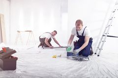 De bemanning die van de huisvernieuwing in binnenland met toolbox en ladder werken stock foto's