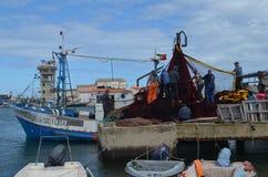 De bemanning van beursseiner verzamelt zijn netten in Olhao-visserijhaven, Algarve, Zuidelijk Portugal stock foto
