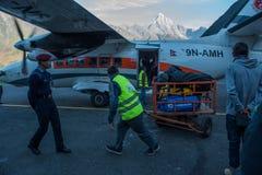 De bemanning van luchtvaartlijn leidt zakken en passagiers met politie bij Lukla-luchthaven royalty-vrije stock foto's
