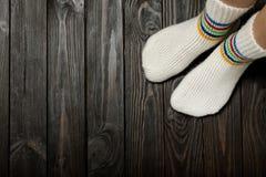 De benen breiden witte wollen sokken op houten donkere achtergrond stock fotografie