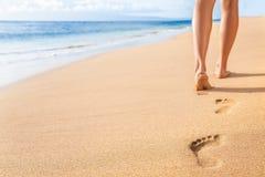 De benen die van de de voetafdrukkenvrouw van het strandzand het ontspannen lopen