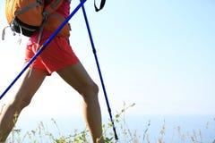 De benen die van de vrouwenwandelaar op kustberg wandelen Stock Fotografie