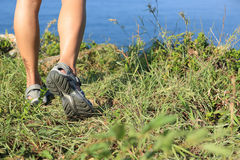 De benen die van de vrouwenwandelaar op kustberg wandelen Stock Afbeeldingen