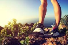 De benen die van de vrouwenwandelaar op kustberg wandelen Royalty-vrije Stock Afbeeldingen