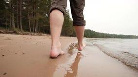 De benen die van de Kaukasische mens op zand dichtbij water gaan stock videobeelden