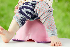 De benen die van kinderen neer van een kamerpot hangen Stock Afbeeldingen