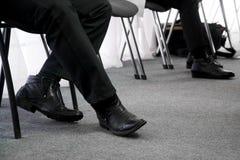 De benen die van de werklozen, op hun draai voor een gesprek wachten, dat op bureaustoelen zit in de gang Werkloosheid en baan stock foto's