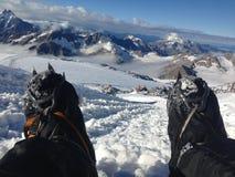 De benen, klimmer zit op een helling overziend de belangrijkste Kaukasische rand royalty-vrije stock afbeeldingen