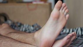 De benen van de man liggen op het bed stock footage