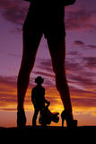 De benen van de silhouetvrouw met het zadel van de hielen weg cowboy Royalty-vrije Stock Foto's