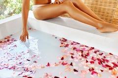 De benen van de vrouw De voet van de vrouw in het water Rose Flower Bath De Behandeling van de kuuroordhuid Royalty-vrije Stock Foto