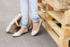 De benen van de vrouw in jeans en vlakke schoenen Stock Foto's