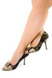 De benen van de vrouw in zwarte schoenen die op witte B worden geïsoleerdn stock foto's