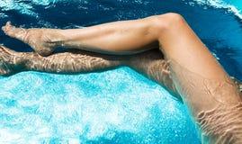 De benen van de vrouw in zwembad stock foto's