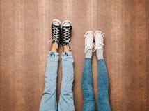 De benen van het jonge manierpaar in jeans en tennisschoenenvoeten omhoog op de muur binnen Warme kleur Royalty-vrije Stock Foto's