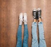 De benen van het jonge manierpaar in jeans en tennisschoenenvoeten omhoog op de muur Sluit omhoog binnen Warme kleur Royalty-vrije Stock Afbeelding