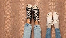 De benen van het jonge manierpaar in jeans en tennisschoenenvoeten omhoog op thewall Sluit omhoog binnen Warme kleur Stock Afbeeldingen