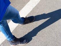 De benen van het meisje in jeans en laarzen geven een schaduw op het asfalt royalty-vrije stock afbeeldingen