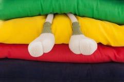 De benen van het stuk speelgoed tussen kleurrijke hoofdkussens Stock Foto