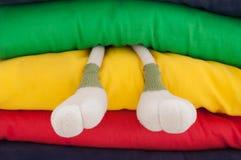 De benen van het stuk speelgoed tussen kleurrijke hoofdkussens Royalty-vrije Stock Afbeeldingen