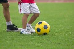 De benen van jonge geitjes schoppen voetbal stock foto's