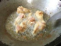 De benen van kip het grijpen neer zijn gebraden in hete olie Stock Foto