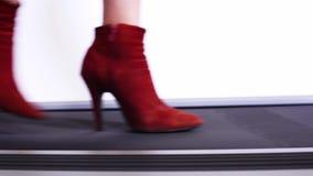 De benen van slanke vrouwen in rode laarzen met dunne hielen die op de loopbrug lopen die een nieuwe inzameling van schoenen voor stock footage