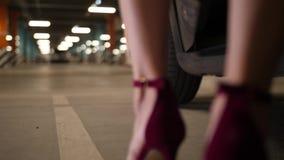 De benen van de vrouw in hoge hielen die uit auto stappen stock video