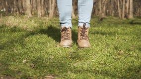 De benen van vrouwen in jeans en laarzen, die op het heldergroene gras lopen stock video