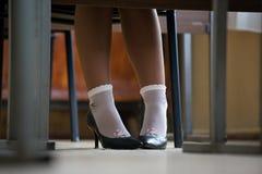De benen van vrouwen in sokken en hielen stock fotografie