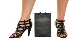 De benen van vrouwen in wreathy schoenentribune achter zak stock afbeelding