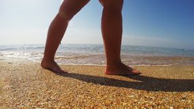 De benen van vrouwen zijn op het zandige strand waarop de golf de voetafdrukken reinigt stock videobeelden