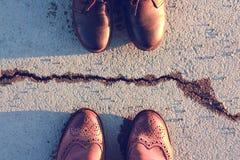 De benen worden geschoeid in leerschoenen van bruine en zwarte kleur, die door een barst op het asfalt worden gescheiden royalty-vrije stock foto