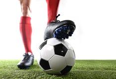 De benenvoeten van voetbalster in rode sokken en zwarte schoenen die met de bal het spelen op groen gras stellen werpen royalty-vrije stock foto