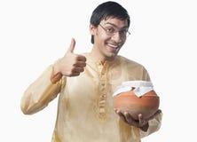 De Bengaalse mens die een pot van rasgulla houden en duimen tonen ondertekent omhoog Stock Foto's