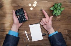 De berekening van de geldmunt Calculator en leeg notastootkussen op bureau stock afbeelding