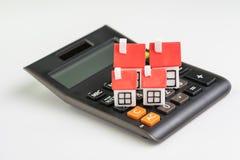 De berekening van huiskosten, hypotheek en huislening of het concept van de onroerende goederenprijs, groep miniatuurhuizen met r stock foto
