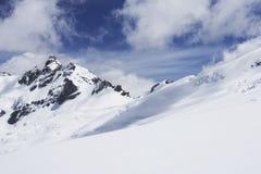 De berg bereikt onder sneeuw een hoogtepunt stock afbeeldingen