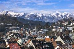De berg en de huizen in de sneeuw en een stad in de Alpen in de winter stock foto's