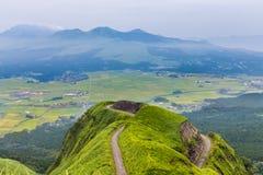 De berg van de Asovulkaan en landbouwersdorp in Kumamoto, Japan stock fotografie