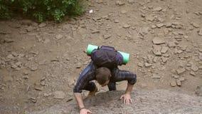 De bergbeklimmer met een rugzak beklimt op een steile rots stock videobeelden