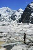 De bergbeklimmer van de vrouw dichtbij ijzige stroom. Royalty-vrije Stock Foto's