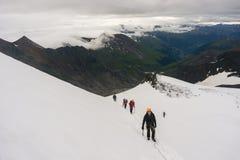 De bergbeklimmers roped omhoog op de gletsjer Stock Foto