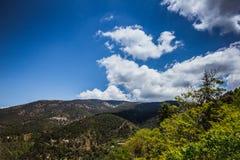 De bergen in Cyprus met witte wolken behandelden schone blauwe hemel stock foto