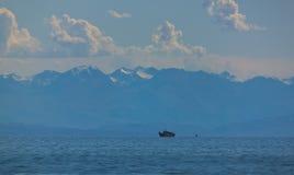 De bergen in de nevel van het meer met een boot Stock Fotografie